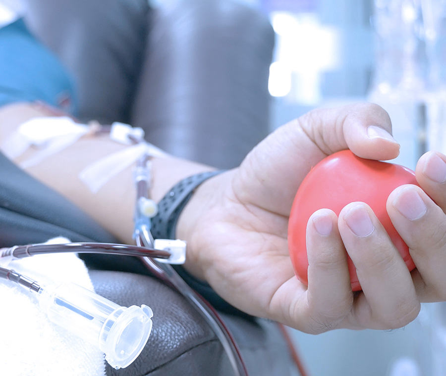 Hand squeezing rubber ball while giving blood