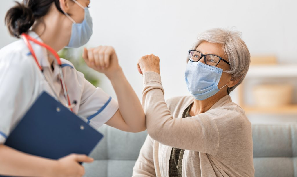 Patient and staff with masks on touching elbows