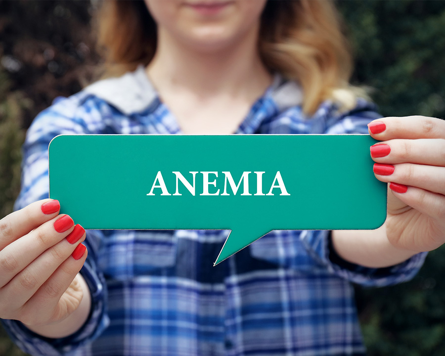 Woman holding a sign that reads ANEMIA