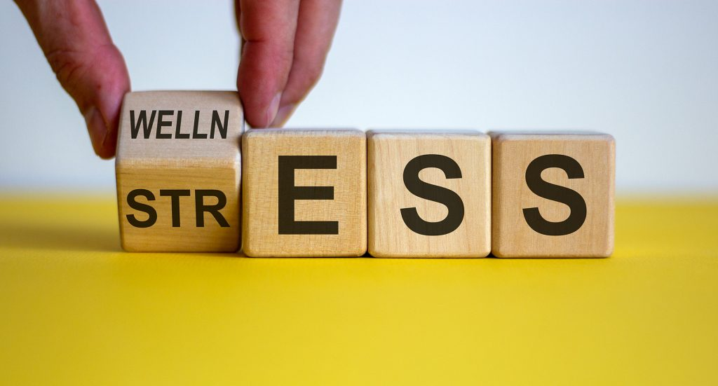 Four wooden blocks spelling out the word stress on a yellow surface