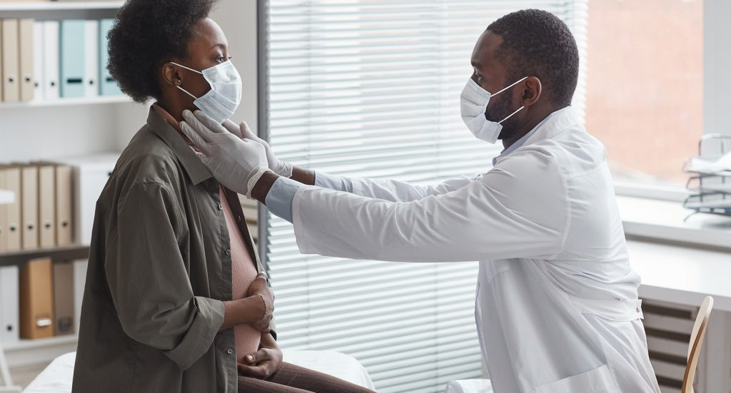 masked doctor diagnosing masked, pregnant woman