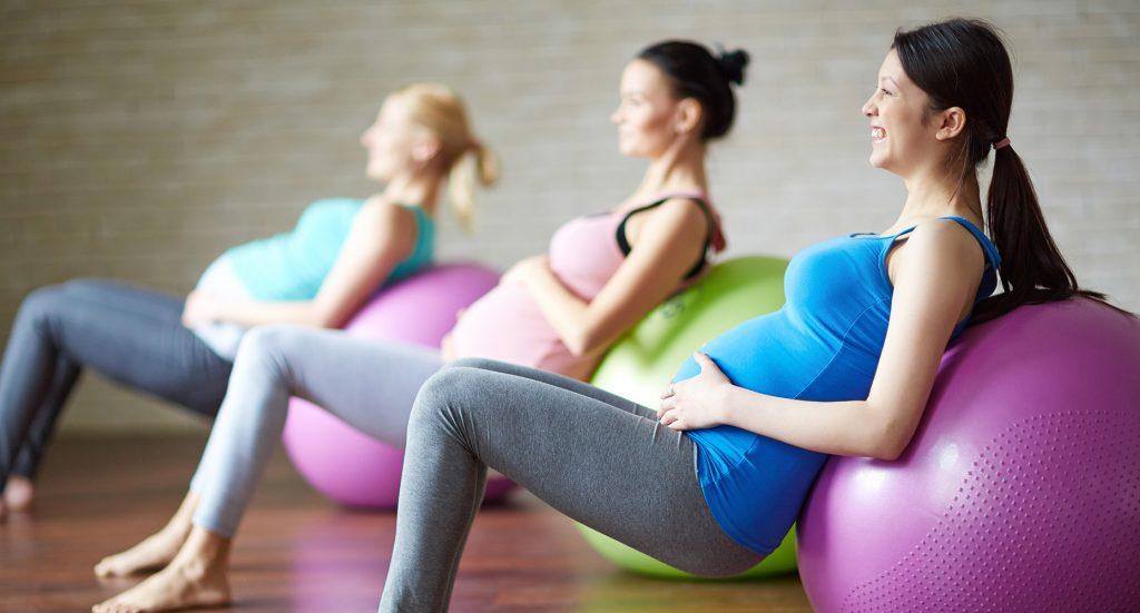 pregnant women leaning their backs against exercise balls