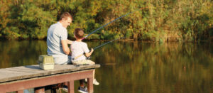 Father and son looking at each other while fishing