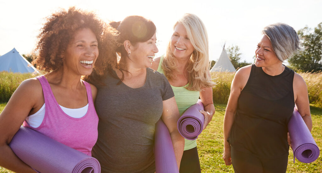 four women holding rolled up yoga mats walking on grass