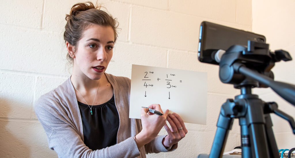 teacher holding up a math equation in front of a self camera setup