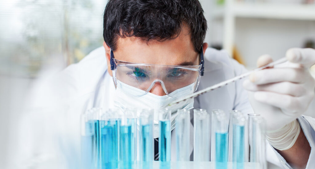 lab physician analyzing multiple tubes filled with blue liquid substance