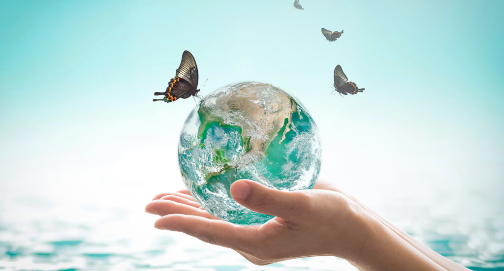 A miniature earth surrounded by butterflies held within the palm of a hand