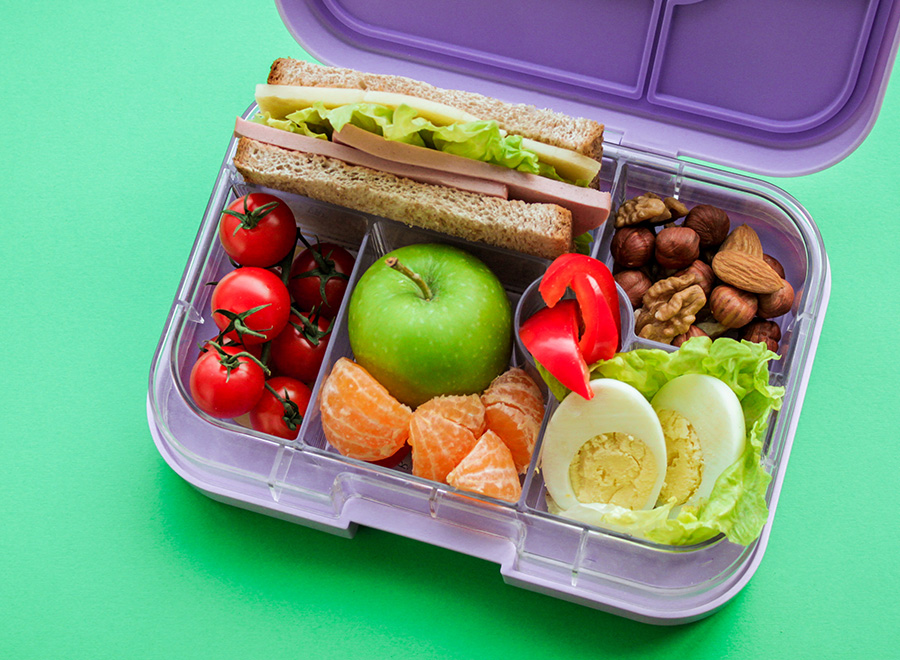 Lilac lunch box with compartments in which-useful food for lunch and snack: sandwich, vegetables, fruits, nuts on a light green background. Concept of healthy food, snack for adults and children